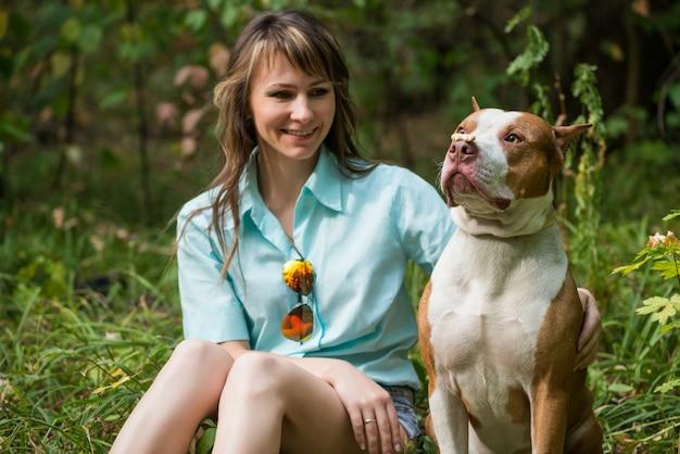 Веселая дама сидит на траве с собакой питбуль.