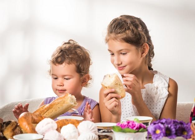 面白い小さな子供たちは焼きたてのパンやロールパンを食べる