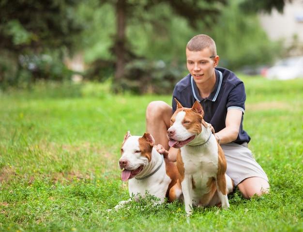 Радостный человек, сидящий на траве с собаками.