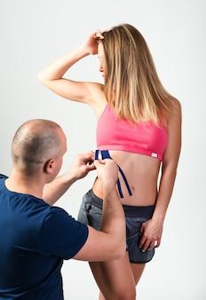 Терапевт клеит терапевтические ленты на живот женщины