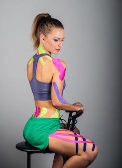 Молодая спортивная девушка сидит на стуле, все в линейках