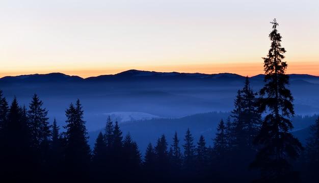 雪と白い煙で覆われた冬の丘と谷のパノラマビュー