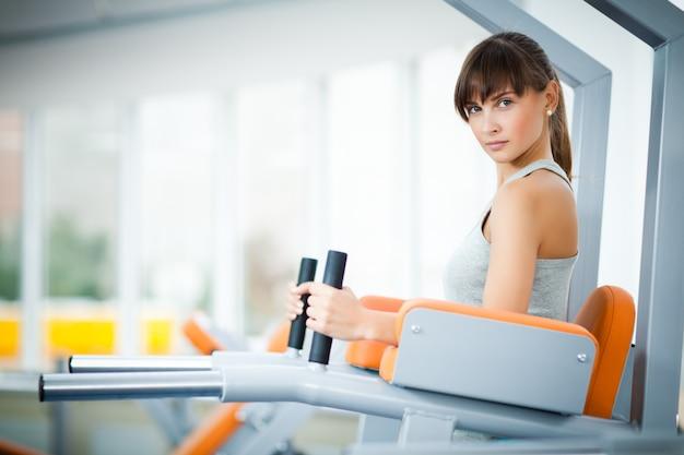 空のジムで脚のフィットネスマシンを使用してトレーニングを行うスポーツウェアの若い美しい女性