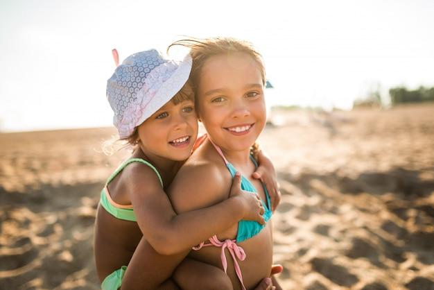 Улыбающаяся маленькая девочка несет свою маленькую очаровательную сестру
