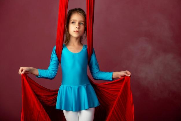 Бесстрашная милая маленькая девочка в синем гимнастическом костюме