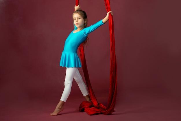 Очаровательная маленькая девочка в синем гимнастическом костюме