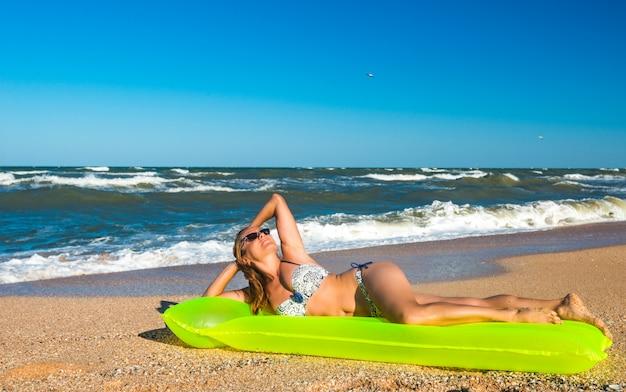 Счастливая женщина на воздухе имеет значение на берегу моря