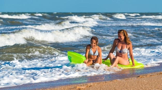 Положительная молодая женщина и ее дочь купаются