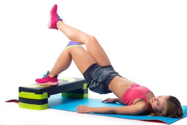 Женщина делает упражнения для ног, лежа на коврике