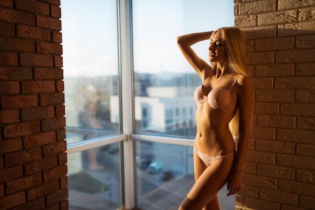 美しい若いスリムな長い髪のブロンドの女性