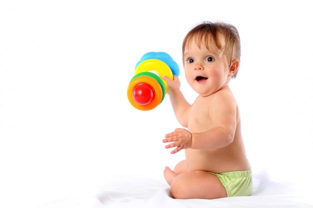 Маленький ребенок играет с игрушкой пирамиды