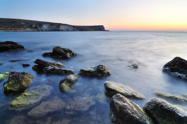 まだ海の水とクリミアの緑の苔で水石の美しいピンクの夕日