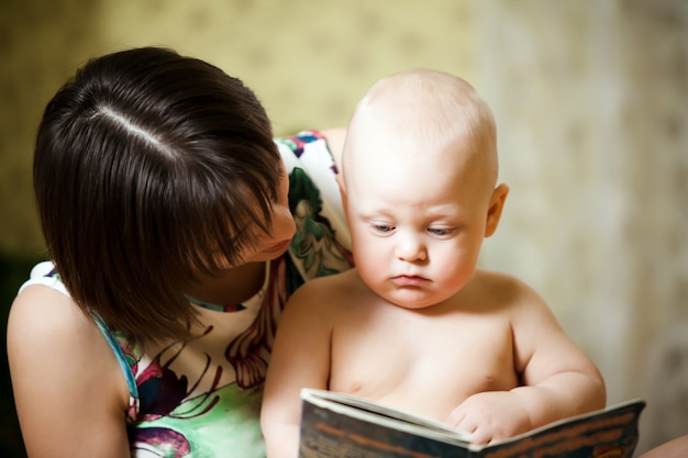Девочка с ребенком с энтузиазмом смотрят на журнал