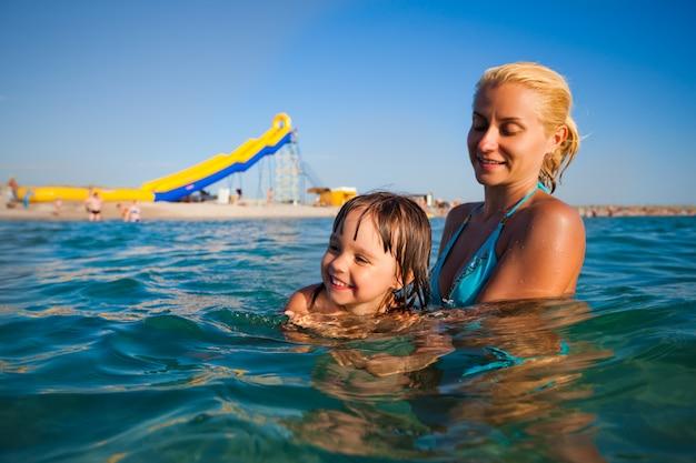 Молодая мать стояла в воде и помогала плавать своей маленькой дочке