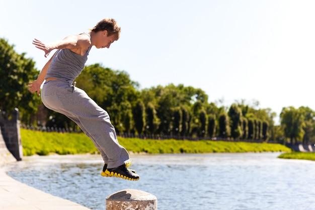 晴れた夏の日に川の堤防を越えて石造りの塀で外のパルクールをジャンプして練習しているスポーツウェアの若い男