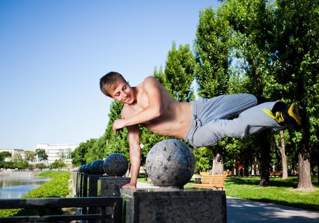 ジャンプして晴れた夏の日に大理石のフェンスに外のパルクールを練習するスポーツウェアの若い男