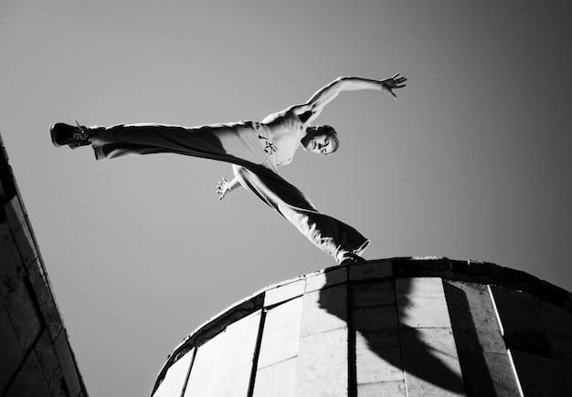 若い男がジャンプして青い空と夏の晴れた日に外の建物の屋根の間でパルクールを練習