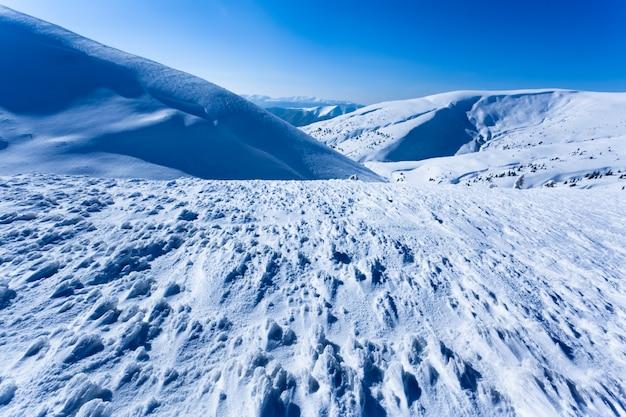 Пейзаж снежной зимней долины и гор в солнечный день