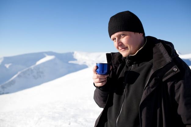 魔法瓶からお茶を飲んで冬の衣類の若い笑みを浮かべて男写真家