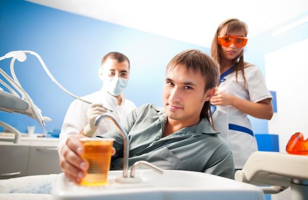 Молодой доктор дантист человек в белой форме и специальной маске и молодая медсестра женщина следственный мужчина пациента в стоматологическом кабинете