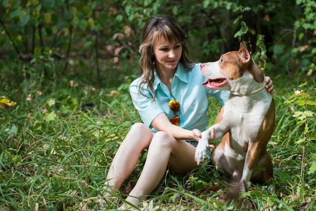 Красивая женщина, сидя на траве с собакой питбуль