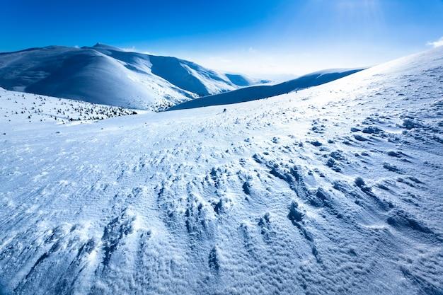 晴れた日に丘に囲まれた冬の渓谷の雪の風景