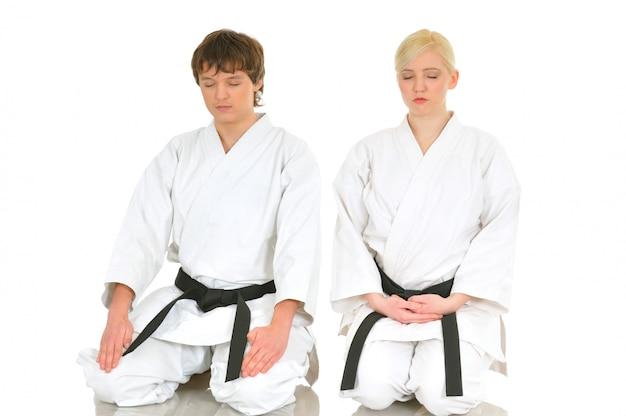Молодая девушка и мальчик, практикующие карате