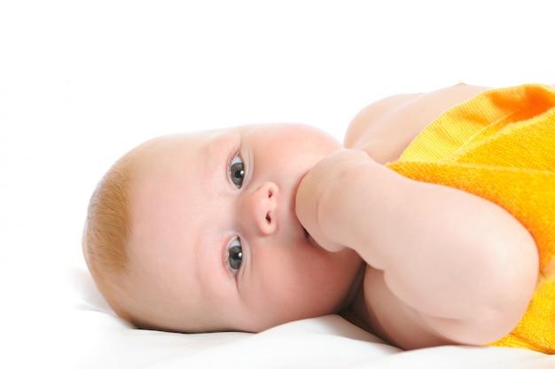 Новорожденный, накрытый желтым полотенцем, лежит в постели