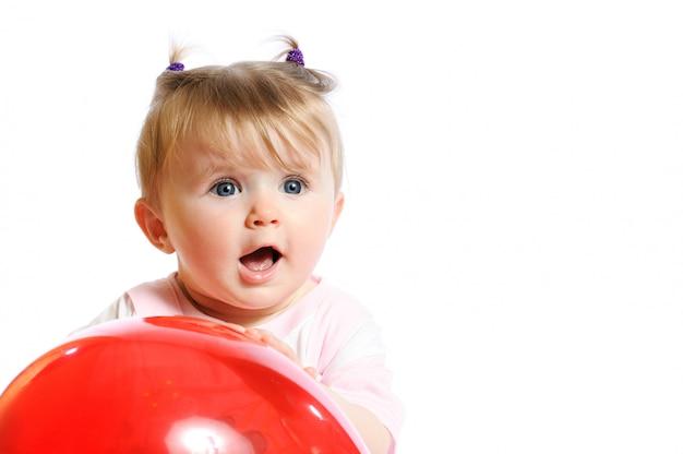 Маленькая девочка держит в руках красный шар