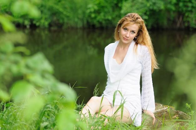 Красивая женщина в белом кружевном платье сидит на земле