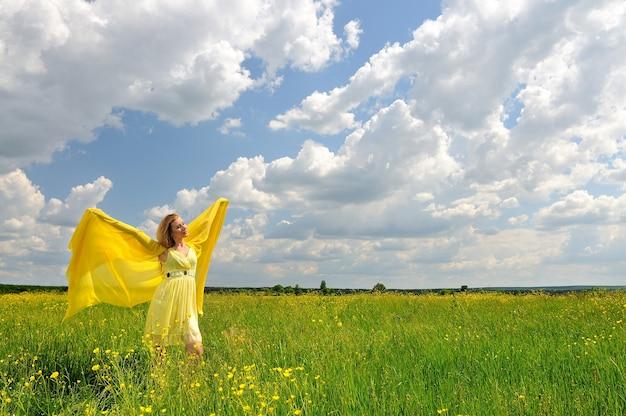 Женщина в желтом платье позирует на поле