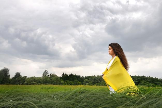 Молодая женщина в белой одежде с желтой шелковой шалью