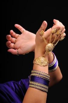 インドの黄金色の宝石と女性の手