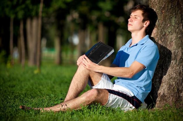 緑の芝生に座っているカジュアルな服装の若い男