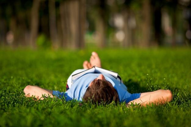 緑の芝生に横になっているカジュアルな服装の若い男