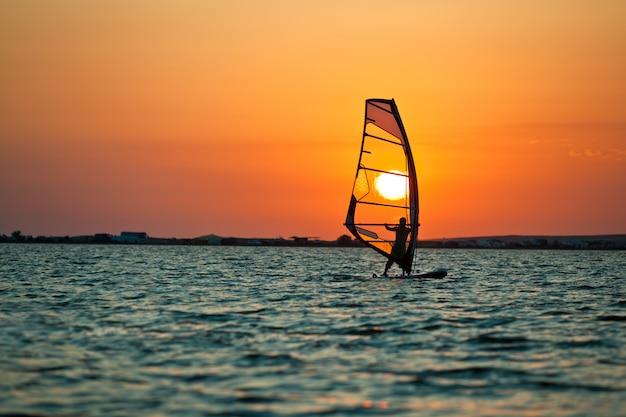 ウィンドサーフィンと黄金の夕日の練習の男