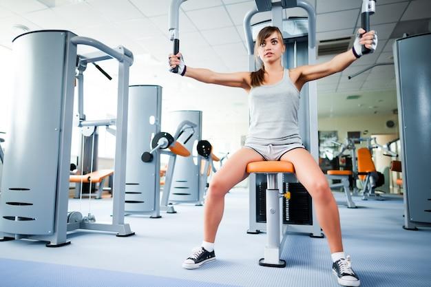 バックグラウンドで空のジムで腕のフィットネスマシンを使用してトレーニングを行うスポーツウェアの若い美しい女性