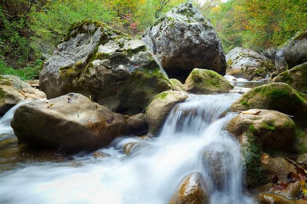Поток холодной горной реки спускается в окружении зеленой травы и скал на берегу