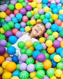 プラスチック製のボールでプールで横になっている子