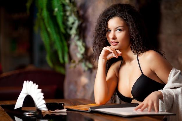 Привлекательная женщина в купальнике сидит за столом