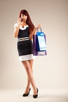 買い物袋を保持しているスタイリッシュな若い女性。