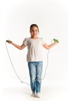 Веселая девушка в повседневной одежде прыгает на веревке