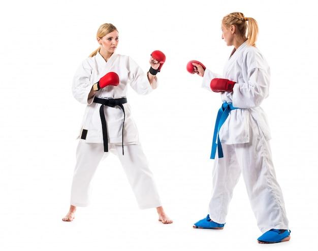 Тренировка по боксу двух молодых женщин на белом