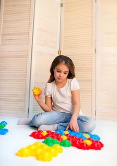 Маленькая любопытная девочка кладет пластиковые пазлы