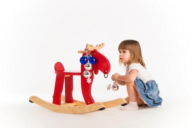 木製のヘラジカと遊ぶ魅力的な女の子