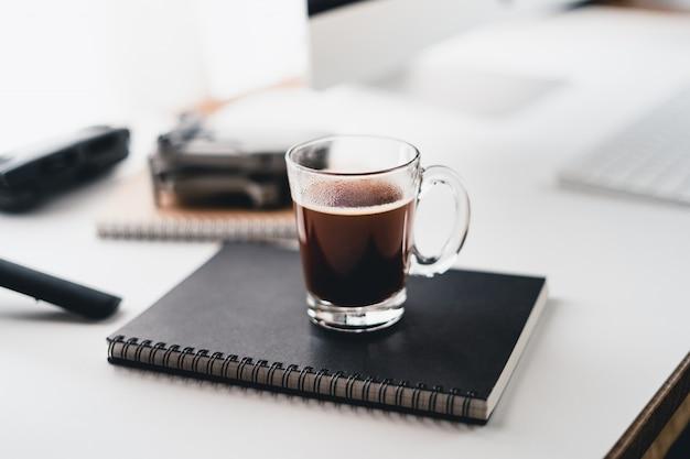 コンピューターの机のカップでホットコーヒー