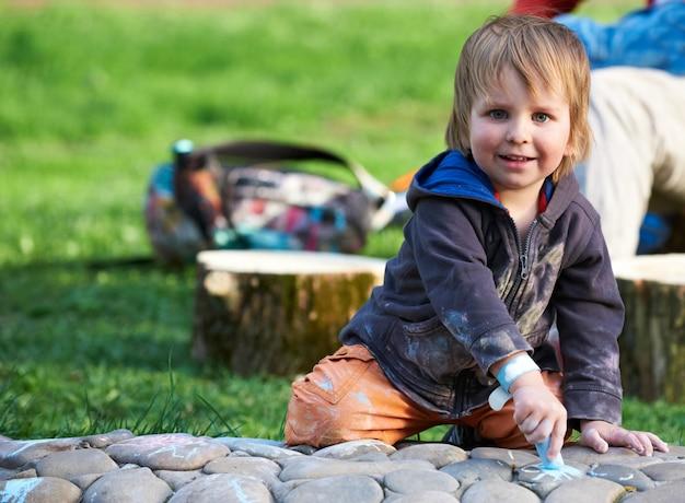 Чертеж мальчика с мелом тротуара в парке.
