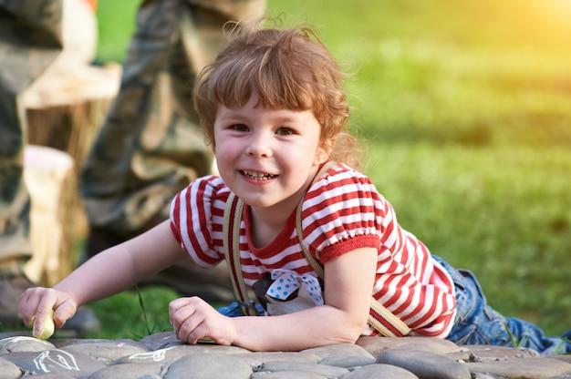 Маленькая девочка, рисование мелом на тротуаре в парке