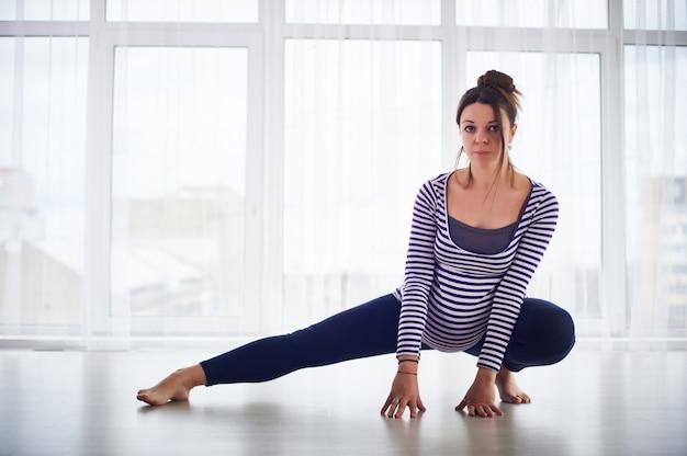 Молодая красивая беременная женщина делает асаны йоги дома.