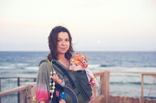 Молодая мать на пляже с ребенком в слинге